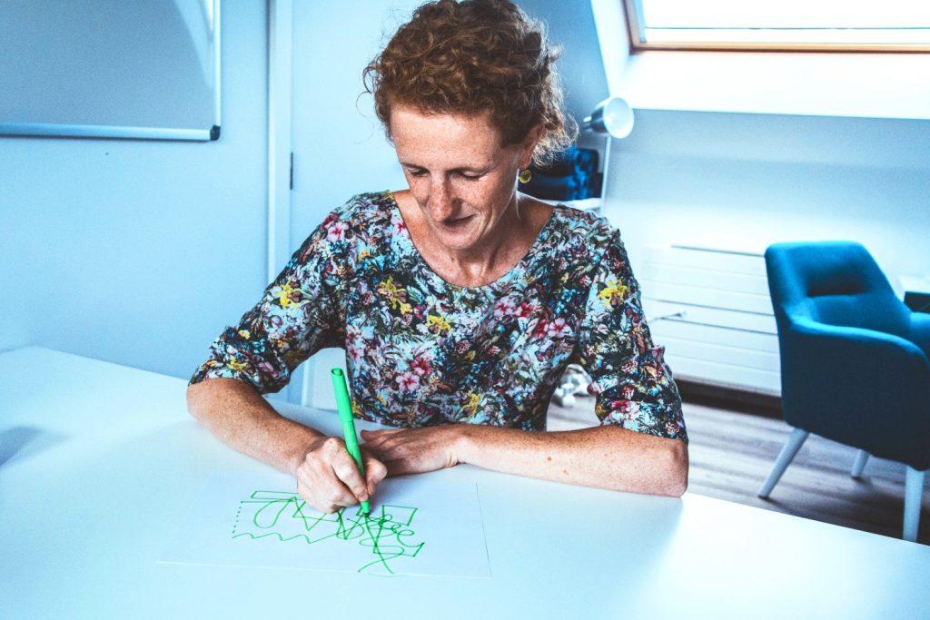 Vrouwelijke klant tekent met gesloten ogen, met een groene stift een intuïtieve lijn op een wit blad als creatieve opdracht bij Tinspireert: individuele sessie aan tafel om in verbinding te komen met zichzelf. (Op de zolder van Tinspireert in Evergem - Gent)