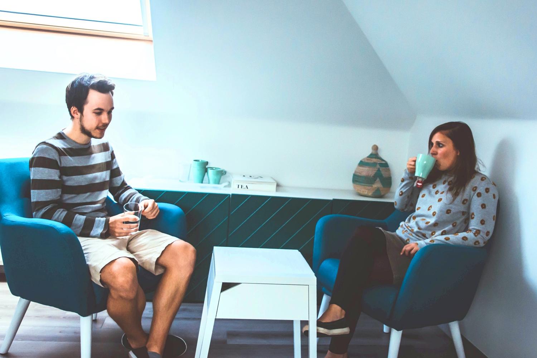 Setting 1-op-1 coaching: kast, thee, tassen, 2 coachzetels en een tafeltje: individuele sessie waar Tinnie (creatief coach) rechts zit en mannelijke klant links. Klant vertelt verhaal. Tinnie luistert en drinkt terwijl van thee. (Op de zolder van Tinspireert in Evergem - Gent)