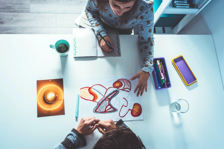 Setting 1-op-1 coaching: creatief aan de slag aan tafel: individuele sessie waar Tinnie (creatief coach) en mannelijke klant de bevindingen en inzichten van de creatieve opdracht bespreken. (Op de zolder van Tinspireert in Evergem - Gent) Foto van boven getrokken.
