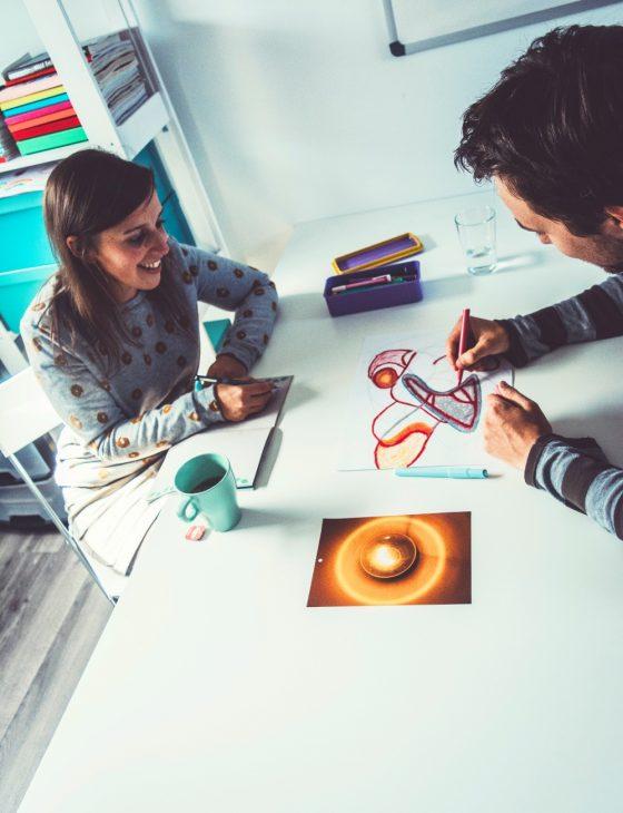 Setting 1-op-1 coaching: creatief aan de slag aan tafel: individuele sessie waar Tinnie (creatief coach) luistert naar wat mannelijke klant vertelt over zijn creatieproces terwijl hij aan het tekenen is. (Op de zolder van Tinspireert in Evergem - Gent)