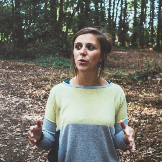 Tinnie (creatief coach) staat in de natuur, in een bos dichtbij Tinspireert in Evergem (Gent), een opdracht uit te leggen.