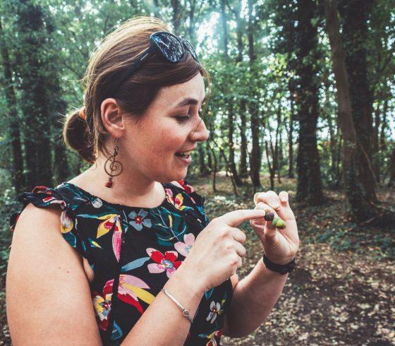 Workshop in de natuur, in een bos dichtbij Tinspireert in Evergem (Gent): vrouwelijke klant toont verwonderd het eikeltje dat ze vond als natuurmateriaal.